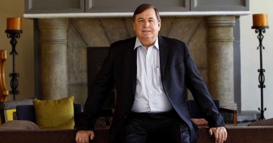 un hombre de traje entero apoyado sobre un sillón