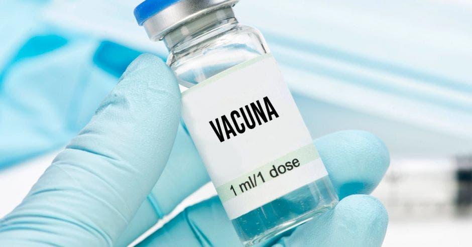Una mano sosteniendo una dosis que dice vacuna en la etiqueta