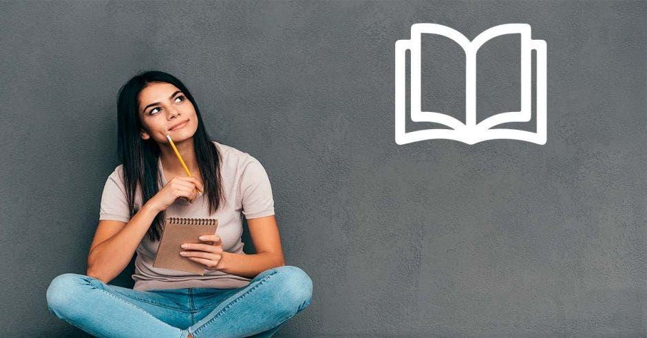 Una mujer joven sentada en el suelo pensando y viendo una imagen de un libro