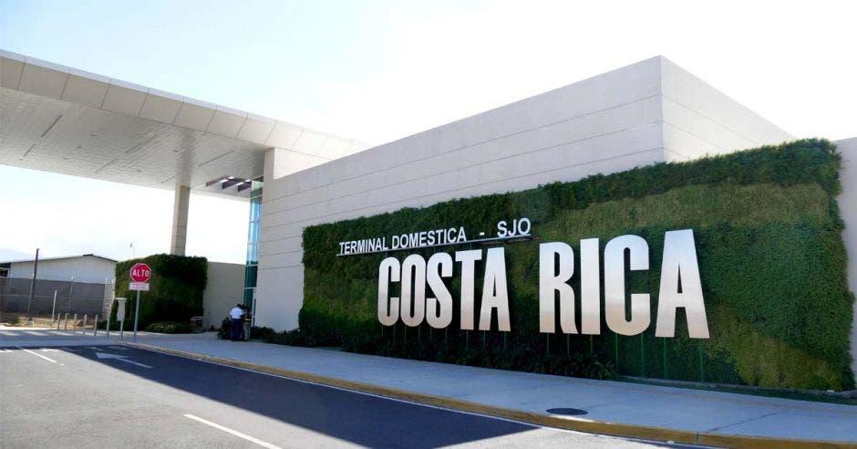 una terminal aeroportuaria con un letrero grande que dice Costa Rica en letras plateadas
