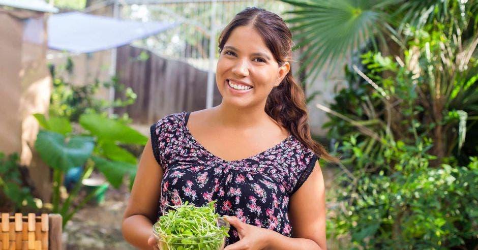 mujer con cabello castaño y blusa negra con flores sosteniendo plantas