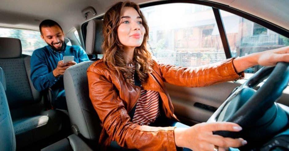conductora de app de transporte manejando y pasajero atrás