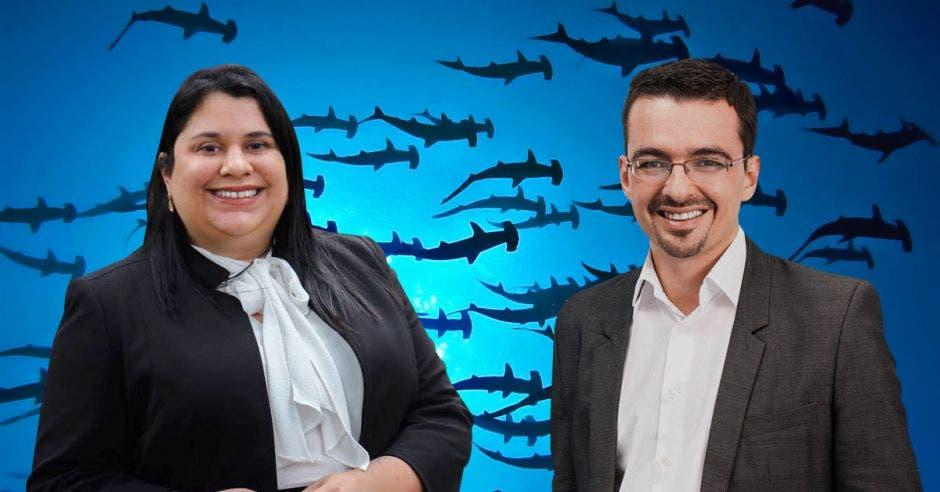 una mujer y hombre de traje oscuro con camisa blanca sonríen sobre una ilustración de tiburones