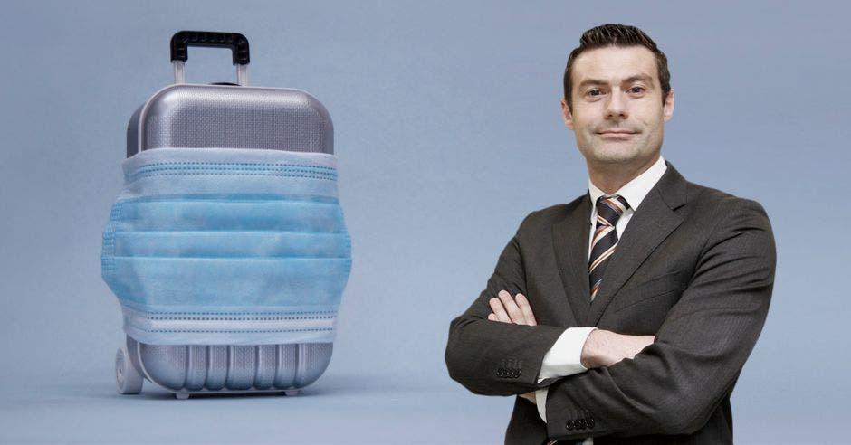Massimo Manzi y una imagen de una maleta con una mascarilla