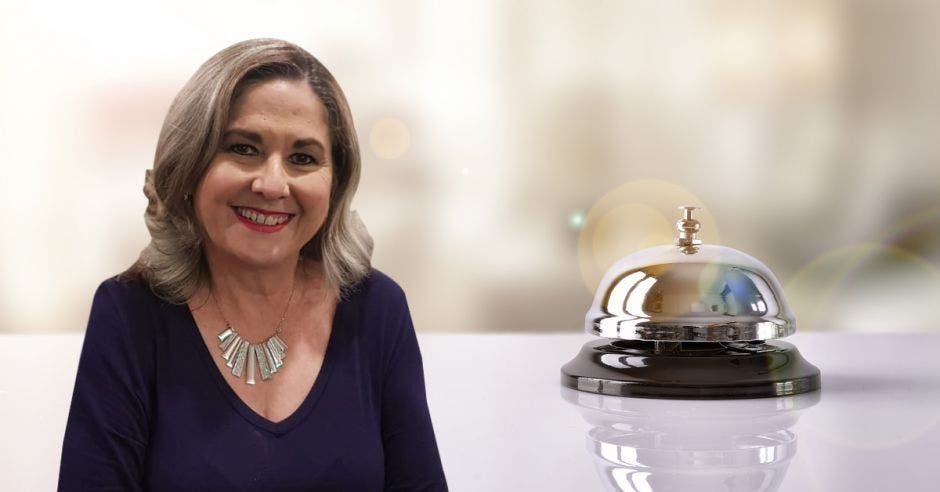 una mujer de blusa morada sobre un fondo de un timbre