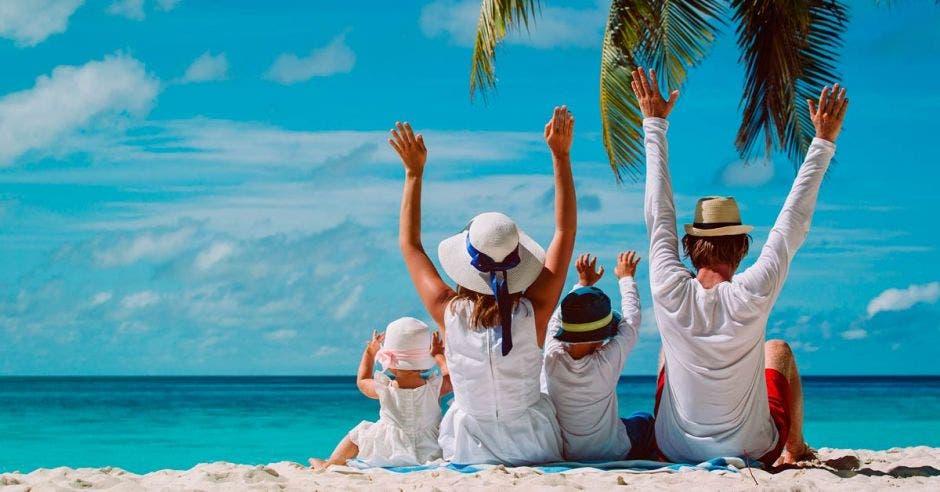 Familia de blanco sentada en la playa