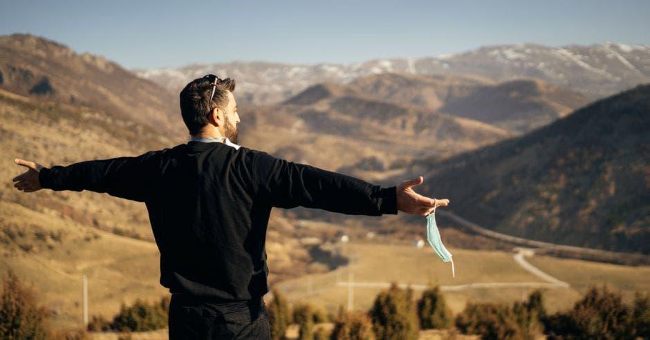 un hombre respira aire fresco en la cima de una montaña