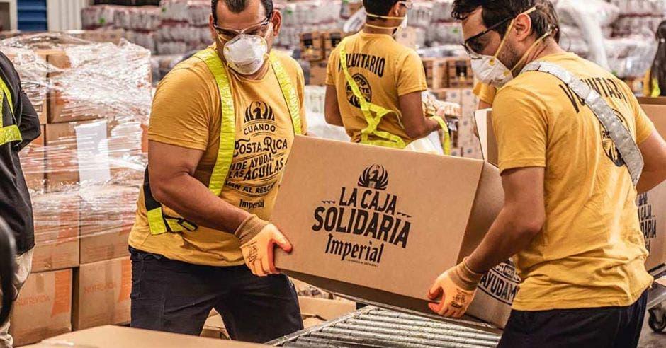 una pareja de hombres carga una caja de cartón para introducirla en un camión
