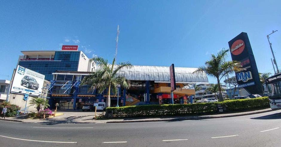 un supermercado amplio con palmeras y arbustos en la entrada