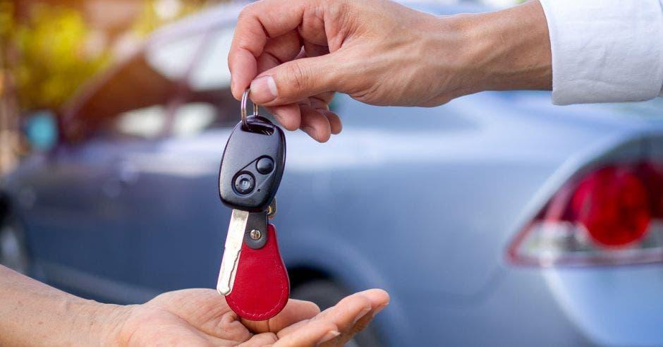 Mano dando llaves de carro a otro