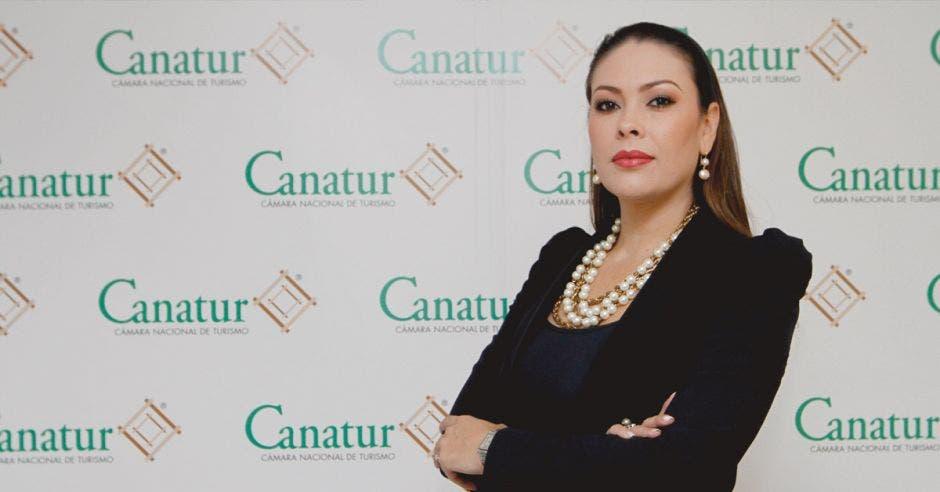 una mujer de traje oscuro sobre un fondo que dice Canatur