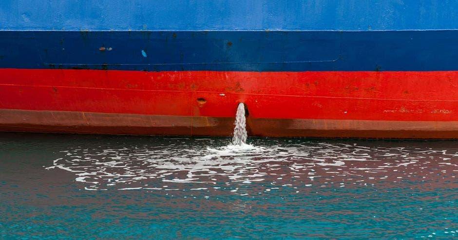 Primer plano de la bomba de achique excretando agua de un barco azul con rojo