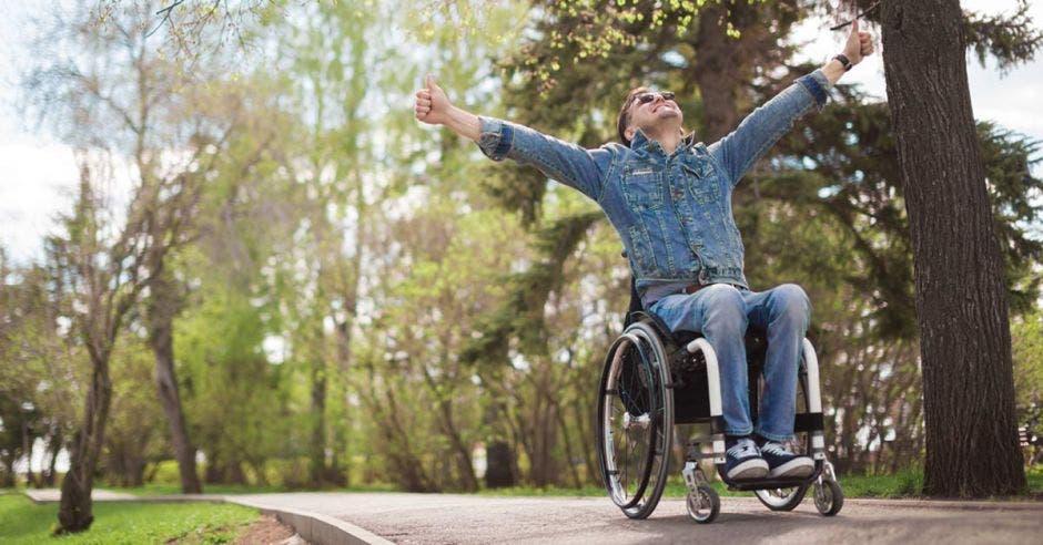 hombre en silla de ruedas levantando los brazos