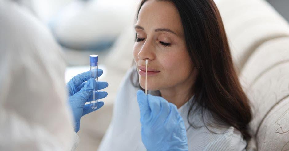 El asistente de laboratorio médico con traje protector se toma la toallita de la nariz de un paciente enfermo en casa. Pruebas de laboratorio para el concepto de coronavirus