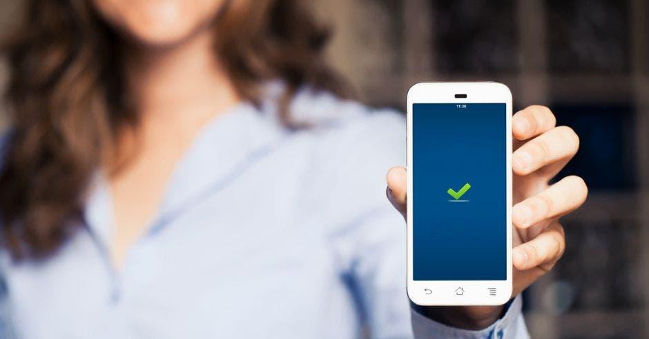 una mujer sostiene un celular con una pantalla azul