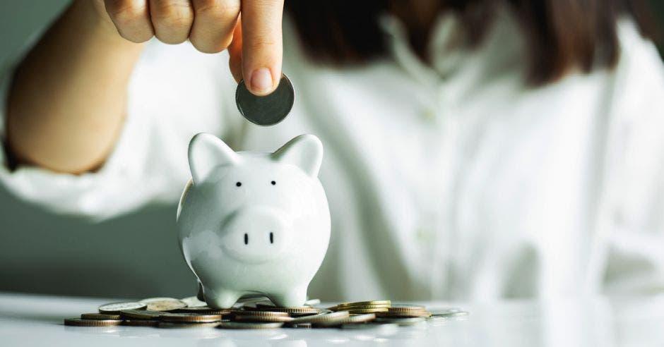 mujer depositando moneda en alcancía blanca de cochinito