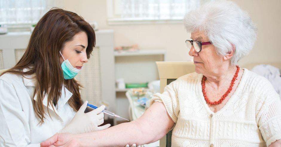 Una adulta mayor recibiendo una inyección