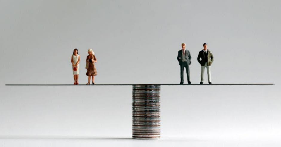 figuras de personas sobre balanza en torre de monedas