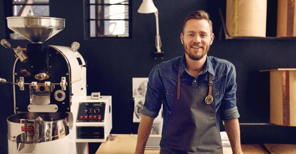 joven empresario junto a máquina de café