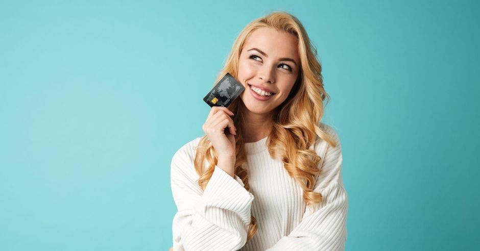 Mujer de pelo rubio con tarjeta de crédito