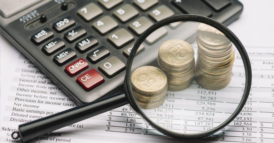 Lupa sobre monedas y calculadora