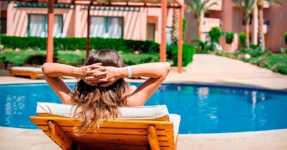 una mujer acostada en una tumbona frente a una piscina