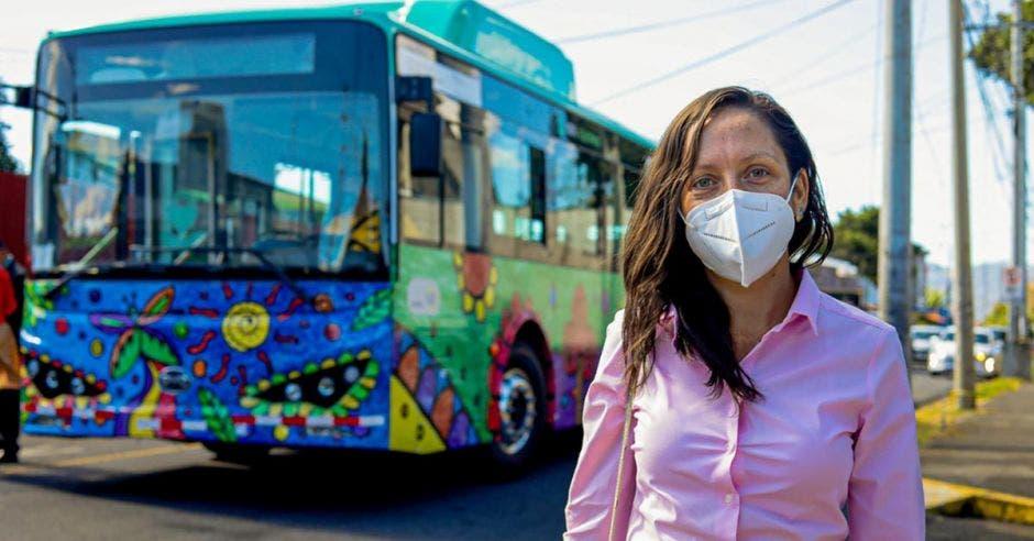 una mujer con mascarilla blanca y blusa rosada posa en frente de un autobús colorido