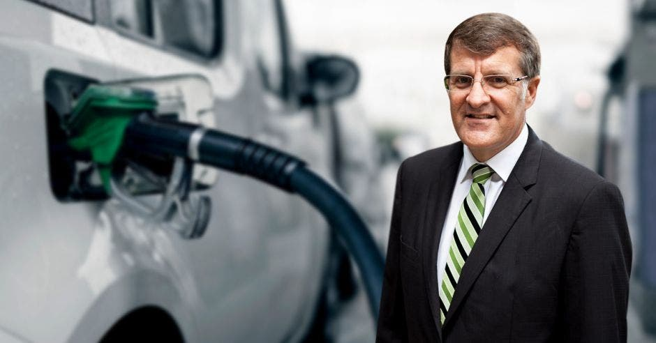 un hombre de saco negro, camisa blanca y corbata a rayas blancas con verdes