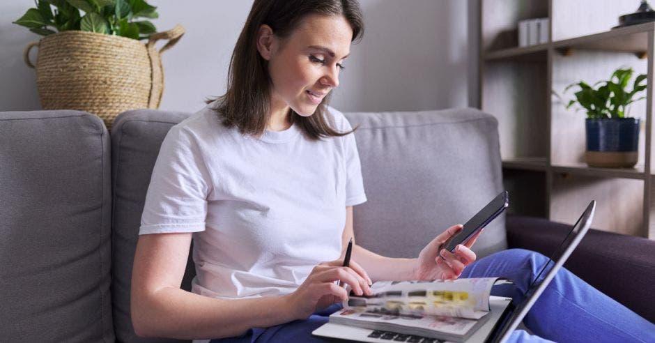 mujer sentada en un sofá gris con laptop en sus piernas hojeando un catálogo