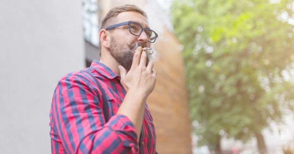 un hombre fuma un cigarrillo de marihuana a las afueras de un edificio