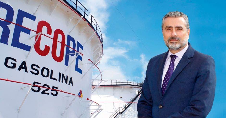 un hombre de saco y corbata junto a un gran tanque de gasolina