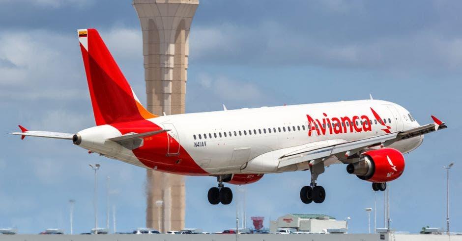 un avión blanco con rojo despegando