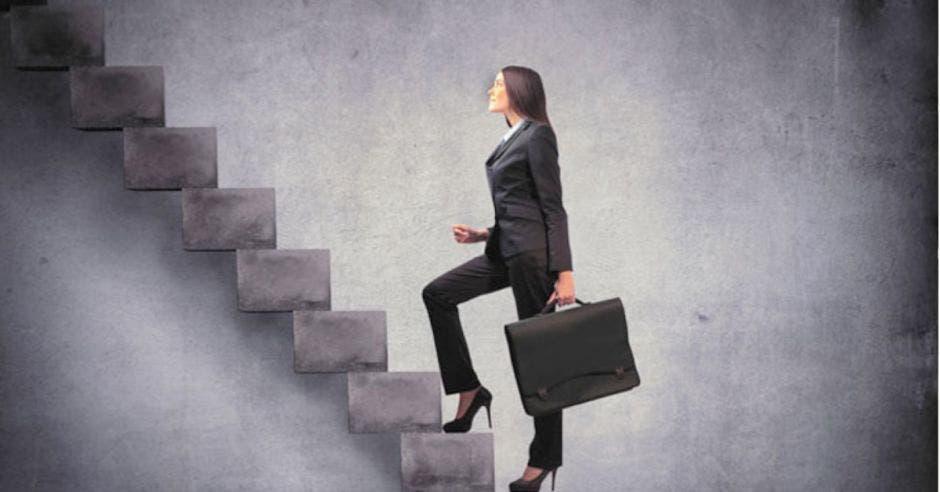 mujer de cabello obscuro con traje negro subiendo escaleras