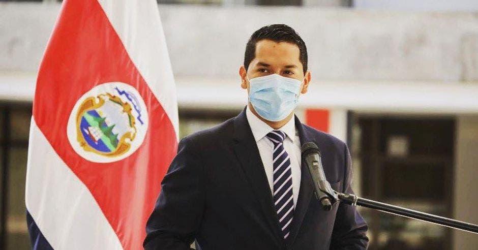 un hombre joven de saco y corbata usando mascarilla