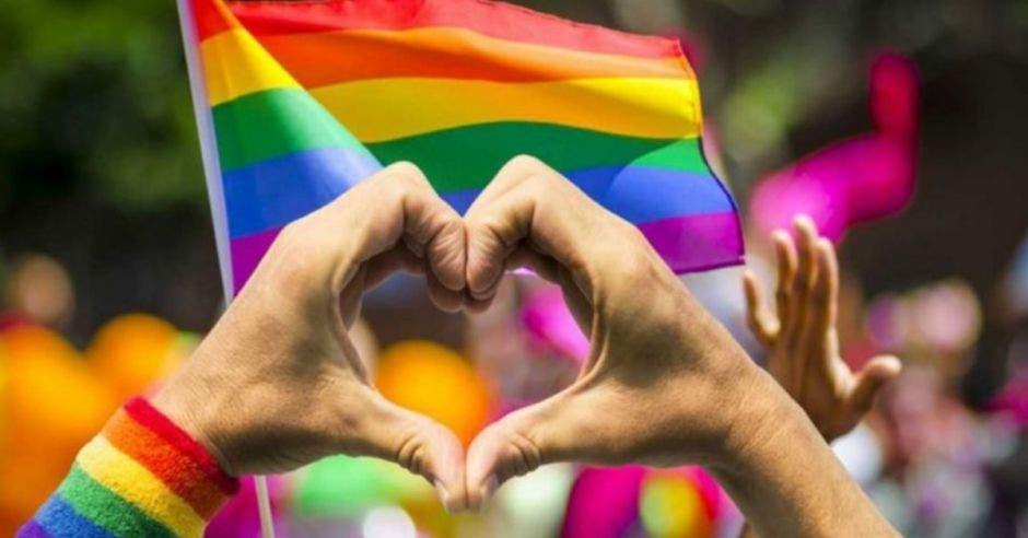 una persona forma un corazón con sus manos. Concepto de personas LGBTI. Banderas multicolor ondean al fondo.