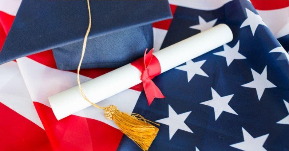 birrete y título sobre bandera de Estados Unidos