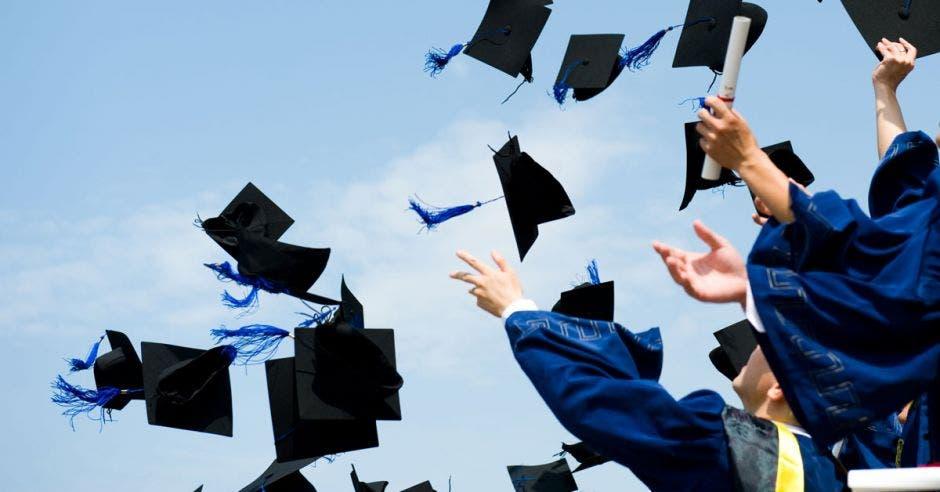 Estudiantes lanzando los birretes al aire