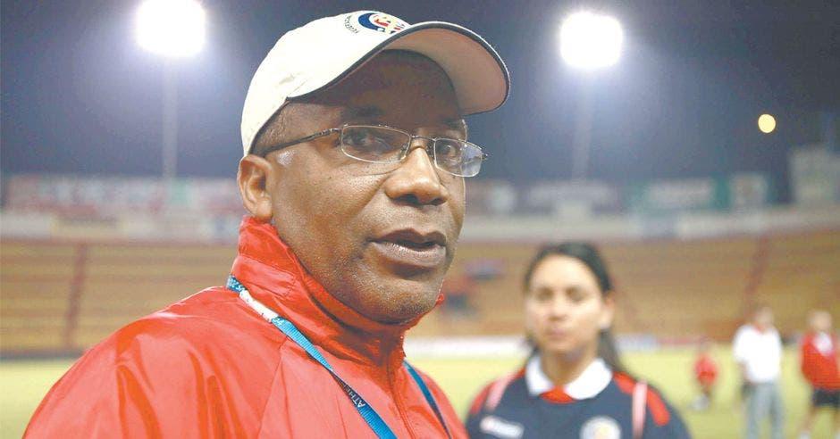 Entrenador de futbol con gorra color blanca y jacket roja
