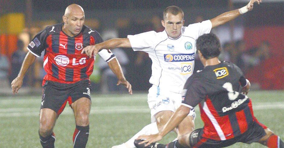 Tres jugadores de futbol que van por el balón