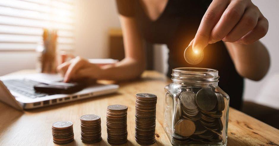 mujer depositando moneda en tarro de vidrio junto a torres de monedas de diferente tamaño
