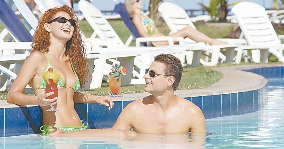 Dos personas dentro de una piscina en un día de verano