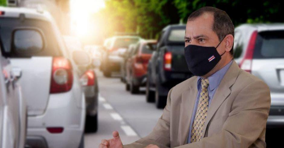 un hombre con mascarilla sobre un fondo de automóviles