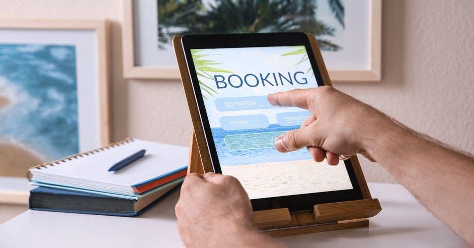 un hombre busca reservas en línea a través de su tablet