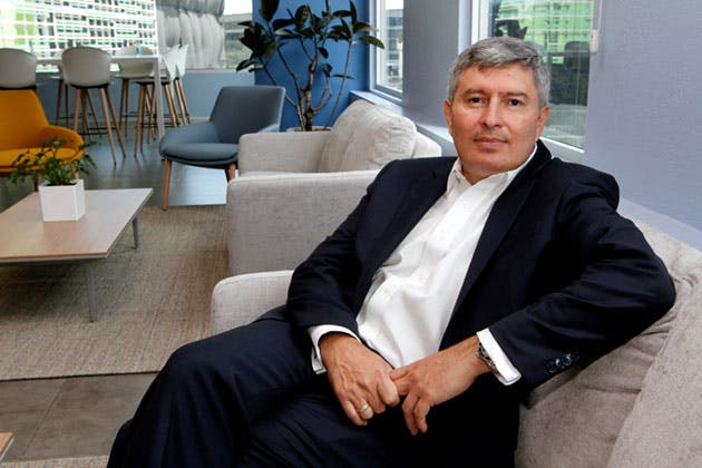 hombre cano con traje obscuro sentado en sofá