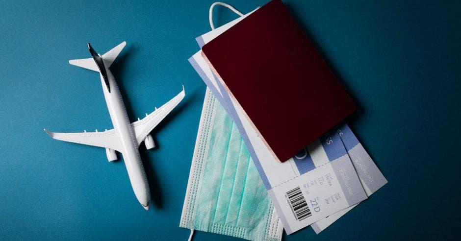 modelo de avión con máscara facial y documentos de viaje