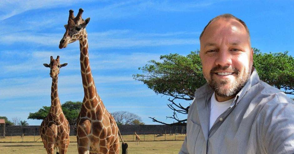 un hombre se toma un selfie con unas jirafas al fondo