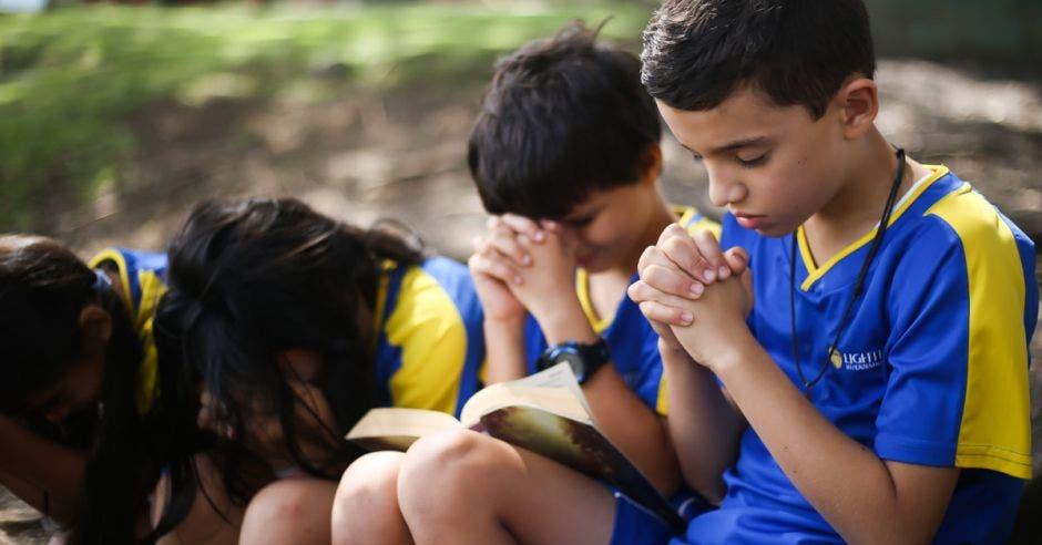 niños con manos entrelazadas orando