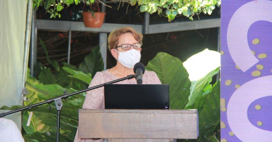 una mujer con mascarilla y anteojos frente a un micrófono