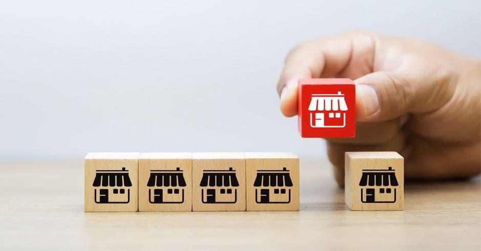 fila de cubos de madera con dibujos de tiendas y mano levantando uno de color rojo