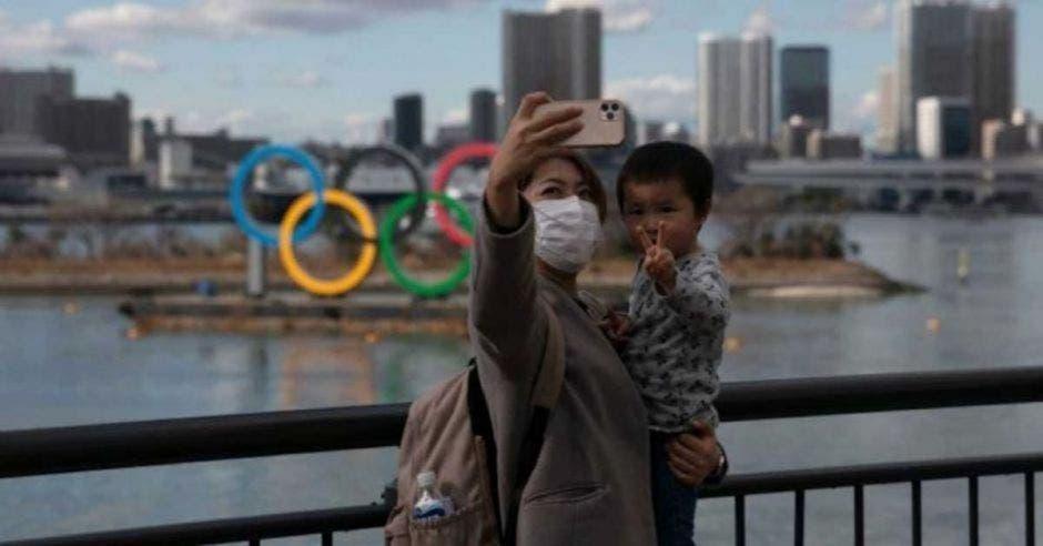 mujer y bebé tomándose selfie frente a símbolo de Juegos Olímpicos